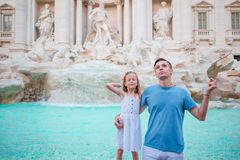 Happy family trowing coins at Trevi Fountain, Rome, Italy for good luck. Little girl and father making a wish to come Royalty Free Stock Photos
