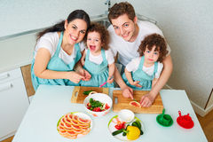 Happy family with twin daughters in the kitchen. Cheerful mother royalty free stock images
