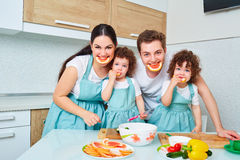 Happy family with twin daughters in the kitchen. Cheerful mother stock photography
