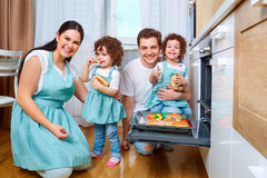 Happy family with twin daughters in the kitchen. Cheerful mother royalty free stock photo
