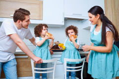 Happy family with twin daughters in the kitchen. Cheerful mother royalty free stock photos