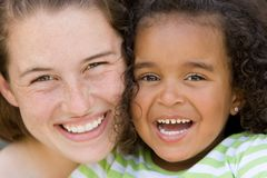 Happy family of two. Freckled young beautiful brunette woman with young big brown-eyed beautiful african american girl child both smiling hugely Royalty Free Stock Image