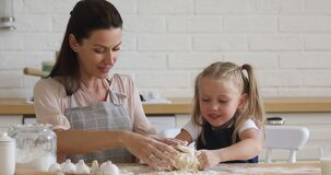 Happy family of two in aprons enjoying baking process together.