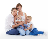 Happy family with two babies. Young parents with sweet  children sit on a white background. Happy family. Six month and four years Royalty Free Stock Image