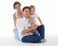 Happy family with two babies. Young parents with sweet  children sit on a white background. Happy family. Six month and four years Stock Photos