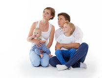Happy family with two babies. Young parents with sweet  children sit on a white background. Happy family. Six month and four years Stock Photo