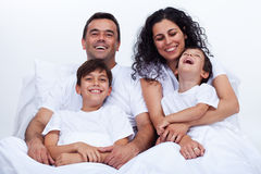 Happy family with two boys cuddling in bed on a lazy morning Royalty Free Stock Image