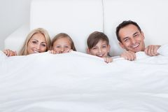 Happy Family With Two Children In Bed Under Cover Stock Photography