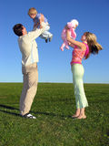 Happy family with two children on blue sky 3. Green grass Royalty Free Stock Photo