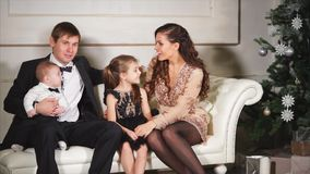 Man, woman and their little kids are resting on a white sofa in Xmas evening stock footage