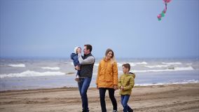 Happy family with two children enjoying a weekend with a kite on the beach. An adult man carries a small child in his arms, his son plays with a kite that stock video
