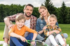 Happy family with two children holding badminton racquets and smiling. At camera outdoors stock photos