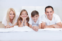 Happy Family With Two Children Lying On Bed Stock Photos