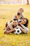 Happy family with two children lying in a pile on grass. In a park royalty free stock photo