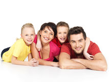 Happy family with two children lying on white floor. Portrait of the happy young family with two children lying at studio on white floor Stock Photo