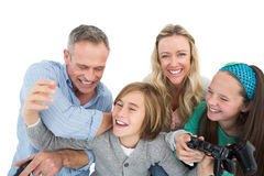 Happy family with two children playing video games. On white background Stock Photo