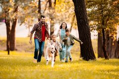 Happy family with two children running after a dog together. In autumn park stock photos