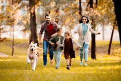 Happy family with two children running after a dog together. In autumn park