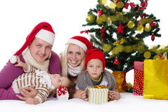 Happy family with two children in Santa hats under Christmas tre Stock Photos
