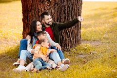 Happy family with two children sitting together on grass in park and taking a selfie. With smartphone stock images
