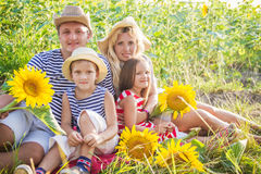 Happy family with two children in sunflowers Royalty Free Stock Images