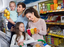 Happy family with two daughters purchasing yoghurts. In supermarket Stock Photo