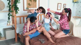Happy family with two daughters rest in bedroom, play and laugh, slow motion. Mom ties hair of girl. Daughter sits on dad neck stock video footage