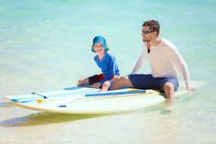 Family at vacation. Happy family of two, father and his son, enjoying active vacation at fiji island resting after stand up paddleboarding Stock Photo
