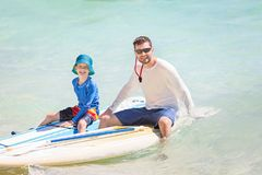 Family on vacation. Happy family of two, father and son, in rashguards enjoying stand up paddleboarding, healthy family activity during summer tropical vacation Royalty Free Stock Photo