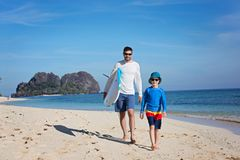 Family at vacation. Happy family of two, father and son, walking at the beach holding surf board, adventure vacation concept Royalty Free Stock Image