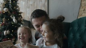 A happy family. Two girls are sitting together with their father on a chair near a Christmas tree and holding gifts. Slow motion stock video footage