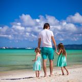 Happy family of two girls and young dad on white Royalty Free Stock Photos