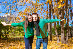 Happy family of two having fun in autumn park on a Royalty Free Stock Photo