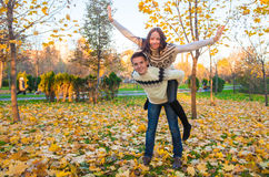 Happy family of two having fun in autumn park on a Stock Photo