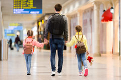 Happy family with two kids in airport have fun waiting for boarding. Happy father with two kids in airport have fun waiting for boarding Stock Images