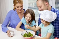 Happy family with two kids cooking at home Stock Image