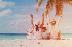 Happy family with two kids hands up on beach Stock Photography