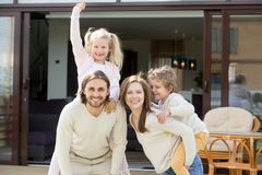 Happy family having fun on house terrace looking at camera. Happy family with two kids having fun together on terrace of modern own new house, smiling parents Royalty Free Stock Image