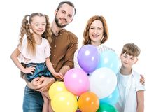 happy family with two kids holding colorful balloons and smiling at camera royalty free stock images