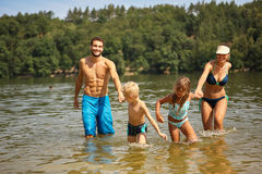 Happy family and two kids in the lake Royalty Free Stock Images
