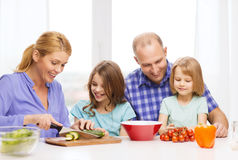 Happy family with two kids making dinner at home. Food, family, children, hapiness and people concept - happy family with two kids making dinner at home Royalty Free Stock Image