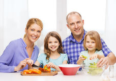 Happy family with two kids making dinner at home. Food, family, children, hapiness and people concept - happy family with two kids making dinner at home Royalty Free Stock Images