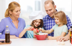 Happy family with two kids making dinner at home. Food, family, children, hapiness and people concept - happy family with two kids making dinner at home Royalty Free Stock Photos