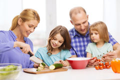 Happy family with two kids making dinner at home Stock Photos