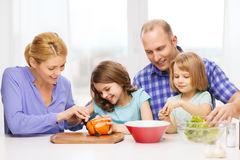 Happy family with two kids making dinner at home. Food, family, children, hapiness and people concept - happy family with two kids making dinner at home Royalty Free Stock Photo