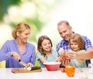 Happy family with two kids making dinner at home. Food, family, children, hapiness and people concept - happy family with two kids making dinner at home Stock Photo
