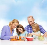 Happy family with two kids making dinner at home. Food, family, children, hapiness and people concept - happy family with two kids making dinner at home Royalty Free Stock Photography