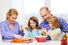 Happy family with two kids making dinner at home Stock Image