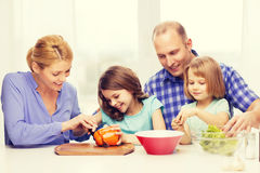 Happy family with two kids making dinner at home. Food, family, children, hapiness and people concept - happy family with two kids making dinner at home Stock Image