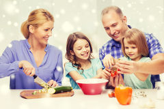 Happy family with two kids making dinner at home. Food, family, children, happiness and people concept - happy family with two kids making dinner at home Royalty Free Stock Image